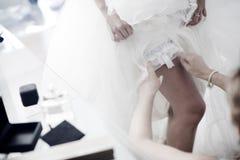Bride putting on wedding bridal garter belt underwear lingerie Stock Image