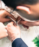 Bride putting on wedding dress. A bride is getting ready for her wedding. The groom is attaches the dress Royalty Free Stock Image