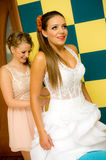 Bride putting on wedding dress. Bridesmaid helping attractive young bride fasten white wedding dress Royalty Free Stock Photo