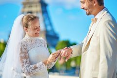 Bride putting wedding ring on a finger of groom Royalty Free Stock Photos