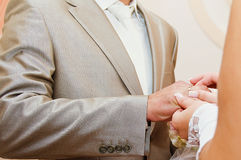 Bride putting a wedding ring on groom's finger Royalty Free Stock Images