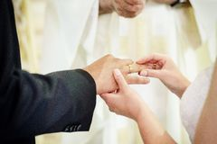 Bride putting a wedding ring on groom`s finger Stock Photo