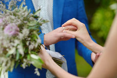 Bride putting wedding ring on groom's finger Royalty Free Stock Photography