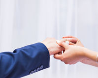 Bride putting a wedding ring on groom's finger close-up Royalty Free Stock Photography