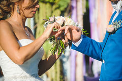 Bride Putting Wedding Ring on Groom`s Hand. Bride putting wedding ring on groom`s finger at ceremony Stock Photography