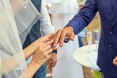Bride putting a wedding ring on grooms finger. Beautiful place for outside wedding ceremony in wood Royalty Free Stock Photos
