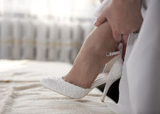 Bride putting on wedding shoes Royalty Free Stock Images