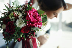 Bride reach out a hand with bouquet decorated with red and white. Flowers a Stock Image