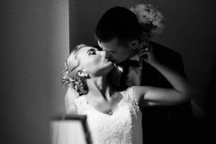 Bride reaches to groom's face in a kiss while sun illuminates th Stock Photo
