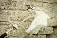 Bride reaching for her bouquet Stock Image