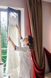 Bride reaching for wedding dress Royalty Free Stock Images