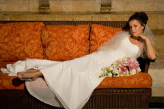 Bride Reclines on Tropical Lounger. A tropical bride reclines on an orange-cushioned lounger Stock Image