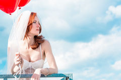 Bride with red balloons on balcony in lingerie Stock Photo