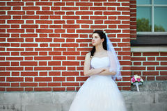 Bride about red brick house Royalty Free Stock Photo