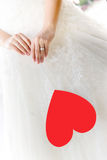 Bride with red heart. Close up bride holding red love heart Royalty Free Stock Image