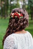 Bride with red natural flowers and greenery in her hair. Portrait of attractive young woman with beautiful hairstyle and stylish h. Air accessory, rear view Stock Image