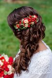 Bride with red natural flowers and greenery in her hair. Portrait of attractive young woman with beautiful hairstyle and stylish h. Air accessory, rear view Stock Photo