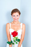 The bride with a red rose. Studio portrait of the bride with a red rose on a gray background Stock Photography