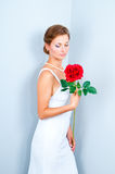 The bride with a red rose. Studio portrait of the bride with a red rose on a gray background Royalty Free Stock Image