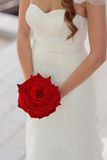 Bride with red rose. Bride in white dress holding a big red rose Stock Photos