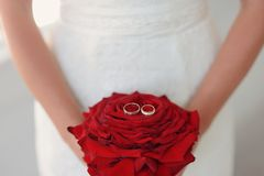 Bride with red rose. Bride in white dress holding a big red rose and wedding rings Royalty Free Stock Image
