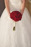 Bride with red rose. In white wedding dress the bride holding a bouquet of red roses Stock Images