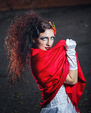 Bride with red shawl. Attractive bride in a wedding dress with bright makeup, red shawl Stock Photo