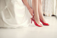 Bride in red shoes. Red shoes for young bride in white dress Royalty Free Stock Image