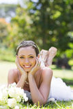 Bride relaxing on grass in the park Royalty Free Stock Photography