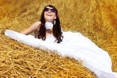 Bride relaxing in hay stack Stock Photo