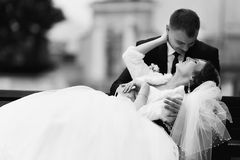 Bride rests on the kneels of groom somewhere on the bench Stock Photo