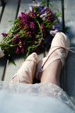 Woman`s feet in ballet slippers with lace hem and a nearby bouquet of wildflowers. stock photos