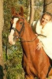 Bride ride on red  horse in forest Royalty Free Stock Images
