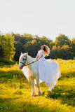 Bride riding a horse on the background of sunset Stock Image
