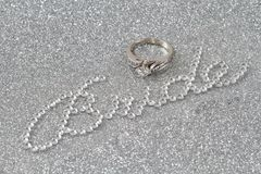 Bride and ring on silver background. White Gold diamond engagement ring as the dot to the letter i in the word bride, made with crystals on a silver background royalty free stock images