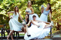 Bride rises her legs up while resting with bridesmaids on the be. Nch royalty free stock image