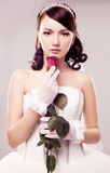 Bride with a rose. Beautiful young bride with a rose,  against grey studio background Stock Image