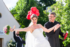 Bride running away with priest after wedding Royalty Free Stock Photos