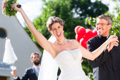 Bride running away with priest after wedding Royalty Free Stock Photo