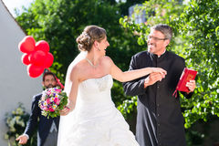 Bride running away with priest after wedding Royalty Free Stock Image