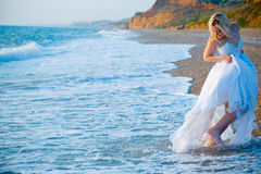 Bride running away from sea waves Stock Images