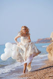Bride running on beach Stock Photo