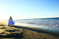 Bride running on beach Stock Image