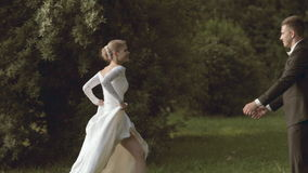 The bride running to the groom and he turns her stock footage