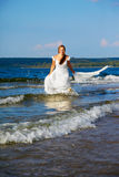 Bride running in waves Stock Photography