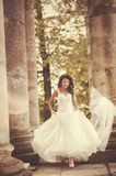 Bride runs between the columnes Stock Photography