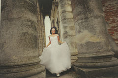 Bride runs between the columnes of the old church Stock Images