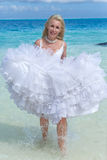 The bride runs on waves of the sea Stock Photos