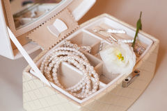 A bride's accessories. A bride's little box of pearl necklace and others accessories with a white flower. Soft lighting Royalty Free Stock Images