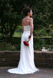 Bride's Back. A beautiful bride looks into the distance as she holds her bouquet Stock Image